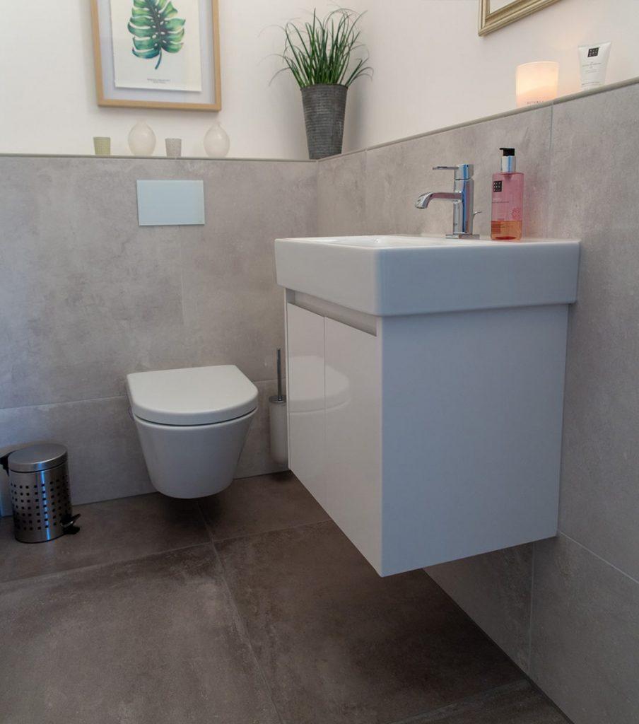 Kleiner Toilettenraum mit großen Fliesen an Wand und Boden